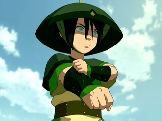 Toph in a warrior outfit against a blue sky. She is in the midst of pulling on a glove. She has a determined look on her face.