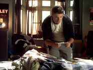 Riley In His Room With A Pile of Clothes Reading A Note